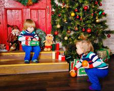 Brother and sister share gifts near Christmas tree. - stock photo