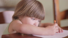 Close up of a little girl sitting at a table and coloring with crayons - stock footage