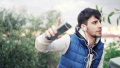 Young man dancing while listening to music on cellphone in park Stock Footage