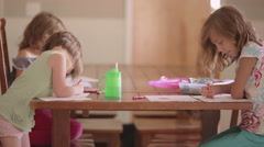 Three sisters coloring at a kitchen table - stock footage