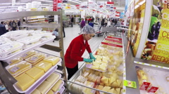 MOSCOW – SEPTEMBER 29, 2015: Employee puts cheese in the hypermarket Stock Footage