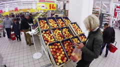 MOSCOW – SEPTEMBER 29, 2015: Blonde chooses apples in the hypermarket Stock Footage