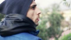 Young, afraid man looking around in park, slow motion 120fps Stock Footage