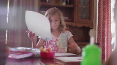 A little girl sitting at a table and coloring with crayons - stock footage