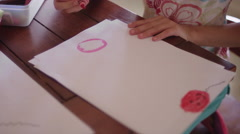 A little girl sitting at a table and coloring with crayons Stock Footage