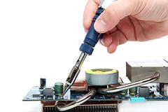 Soldering iron in hand and electric board. - stock photo