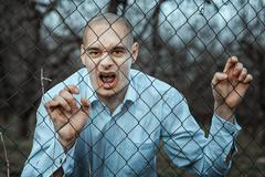 Angry and fearful man grinning over the fence mesh. - stock photo