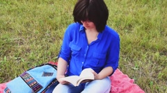 Girl with a book outdoor in summer Stock Footage