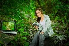 Beautiful young girl using tablet and laptop enjoying excellent connectivity in Stock Photos