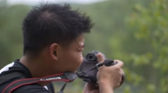 Photographer prepares to take photo-blows bug off arm Stock Footage