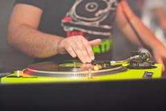 DJ mixing music on vinyl record at the night club Stock Photos