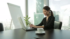 young Asian Business woman at office with laptop, typing, Dolly shot - stock footage