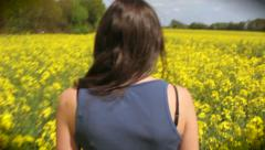 Woman walking through colourful yellow flower field (part of a sequence) Stock Footage