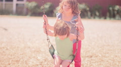 A girl pushing her younger sister on a swingset Stock Footage