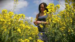 Woman picks flower in field (part of a sequence) Stock Footage