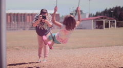 A mother taking pictures of her daughter on a swingset Stock Footage