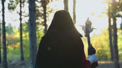 Stock Video Footage of red-haired young female dressed as a witch walking in forest