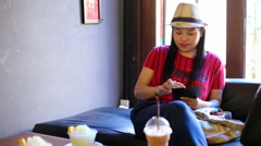 Woman with smartphone drinking ice coffee in cafe Stock Footage