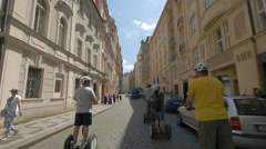 Tourists with electric stand up scooters passing on Maiselova street in Prague Stock Footage