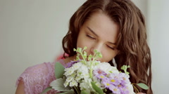 Beautiful girl in a pink dress inhales aroma of a bouquet of flowers. Close-up - stock footage
