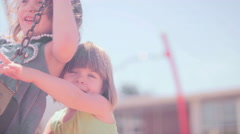 A girl struggles to push her older sister on a swingset Stock Footage