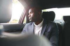African businessman traveling to work in the luxury car Kuvituskuvat