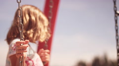A young girl climbs across some hanging ladders at a playground Stock Footage