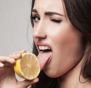 Portrait of woman promoting healthy eating. Beautiful young brunette woman ho - stock photo