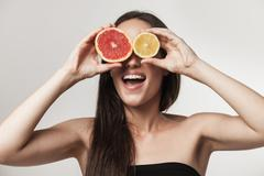 funny portrait of beautiful young brunette woman holding fresh sliced grapefr - stock photo