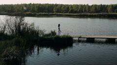 Beautiful brunette in a white dress walks on the bridge Stock Footage