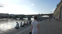 Relaxing on the waterfront, near the Palacky bridge in Prague Stock Footage