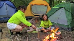 Family camping in the woods marshmallow roasts Stock Footage