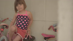 A little girl sitting on her bike on the side of a house and smiling Stock Footage