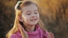 Girl straightens her hair in sunset light Stock Footage