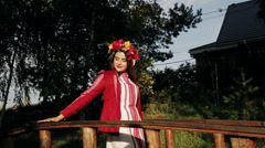 Beautiful girl in Russian national dress with a wreath on his head poses for the Stock Footage