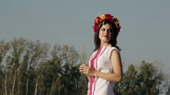 Beautiful girl in Russian national dress with a wreath on his head enjoying the Stock Footage