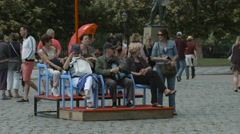 Tourists relaxing on benches in Jan Palach Square, Prague Stock Footage