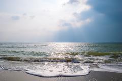 Sea waves on a sandy beach with stormy sky. - stock photo