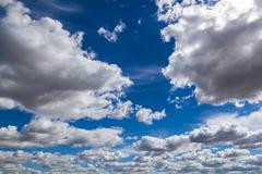Blue sky with cumulus white clouds. - stock photo