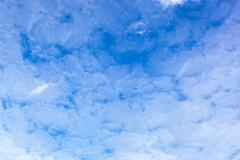 Blue sky with cirrus clouds on a sunny day. - stock photo