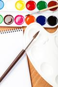 Watercolor paint, brushes and notebook. Stock Photos