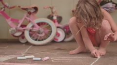A young girl draws a heart on the ground with chalk Stock Footage