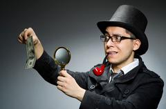 Young detective in black coat with money against gray Stock Photos