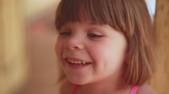Close up of an adorable little girl smiling and looking up at someone Stock Footage