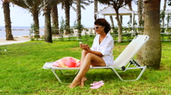Woman talking on phone on vacation. Tropical beach - stock footage