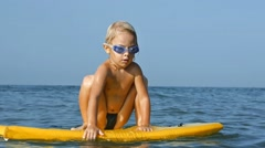 Adorable little child surfboarding on bodyboard in sea and jumping. Slow motion - stock footage