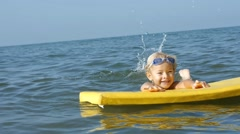 Happy smiling adorable little child enjoying blue sea surfboarding on bodyboard. Stock Footage