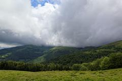 Mountain top with green meadows in the rain clouds. Kuvituskuvat