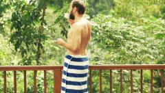 Young man in towel drinking coffee on terrace Stock Footage