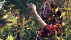 Young female dressed as a witch picking up some berries in forest Stock Footage